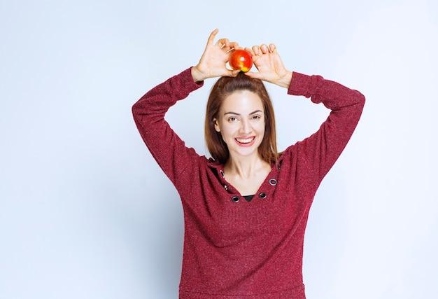 頭上に赤いリンゴを保持している赤いジャケットの若い女性