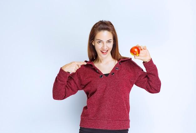 赤いリンゴを保持している赤いジャケットの若い女性