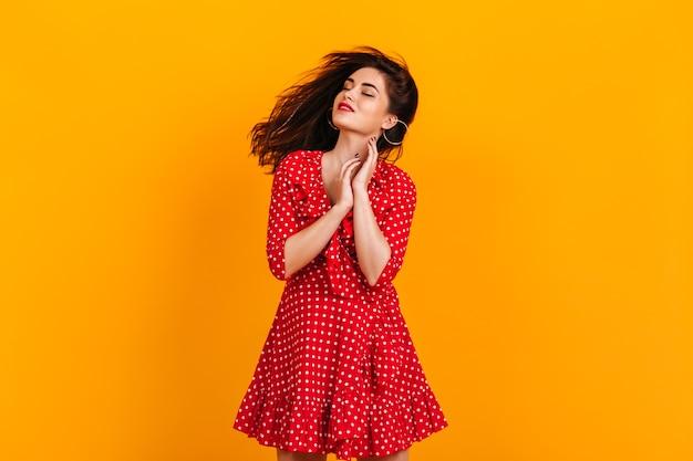 笑顔と目を閉じて黄色の壁にポーズをとって赤い水玉模様の衣装で若い女性。