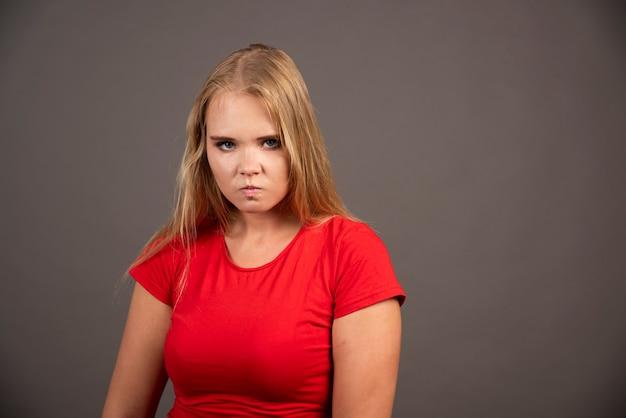 黒い壁にポーズをとって赤いシャツを着た若い女性。