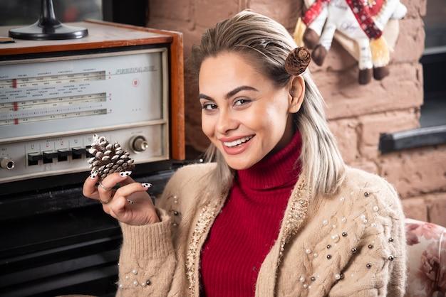 Молодая женщина в красном свитере держит шишку
