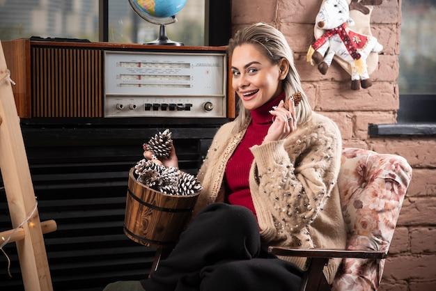 Молодая женщина в красном свитере держит деревянную корзину, полную шишек