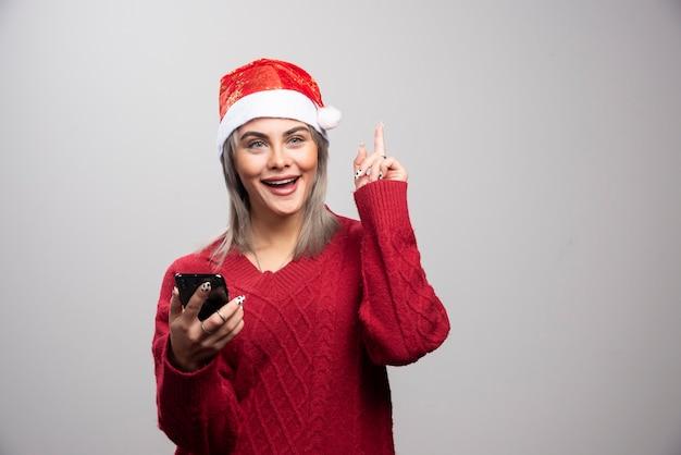 灰色の背景に携帯電話を保持している赤いセーターの若い女性。