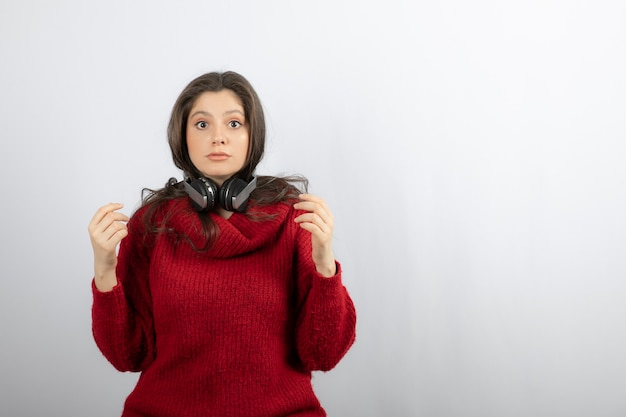 首にヘッドフォンを身に着けている赤いセーターの若い女性。