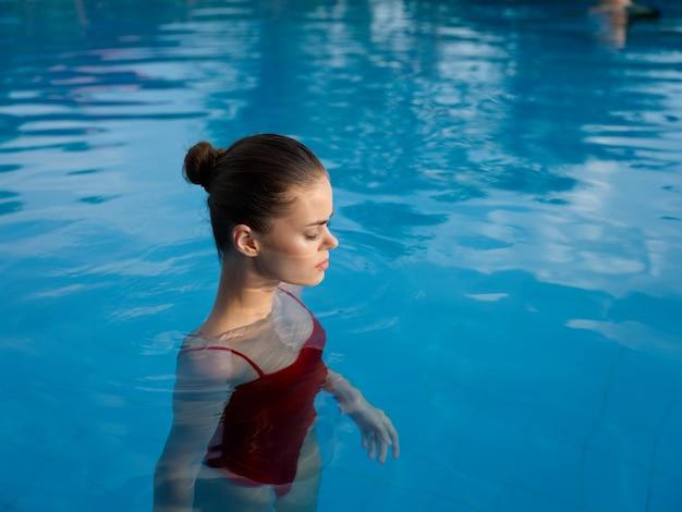 赤い水着の若い女性がプールの透明な水モデルの側面図に立っています