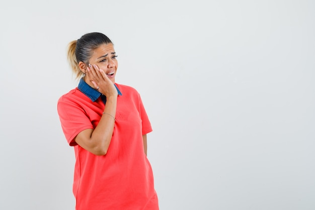 頬に手をつないで、歯痛があり、陰気な顔をしている赤いtシャツの若い女性、正面図。