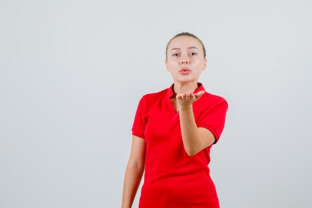 エアキスを送信し、魅力的に見える赤いtシャツの若い女性