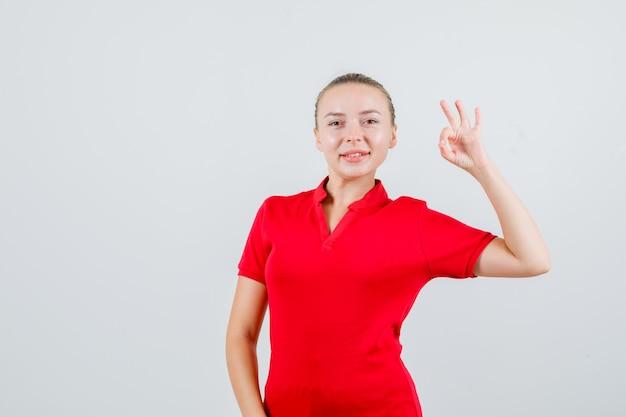 良いジェスチャーを示し、幸せそうに見える赤いtシャツの若い女性