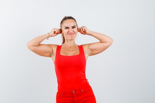 Молодая женщина в красной майке, штаны, потянув за уши и выглядя смешно, вид спереди.
