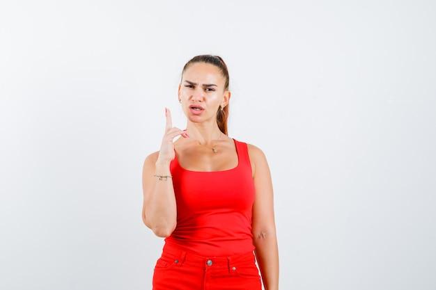 赤いタンクトップの若い女性、ピストルの手のサインを示し、暗い、正面図を表示します。