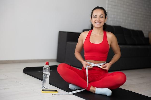 自宅で運動やヨガをしている赤いトラックスーツの若い女性。幸せな陽気な女の子は、足を組んで、ボディ巻尺を使用してマットに座っています。カメラでポーズと笑顔。運動した後、部屋で一人で。