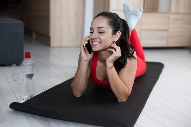 自宅で運動やヨガをしている赤いトラックスーツの若い女性。トレーニングやトレーニングの後にリラックスしたかわいい女の子。スマートフォンを使用してオンラインワイヤレスで話す。現代のテクノロジーとデバイス。トレーニングの後。