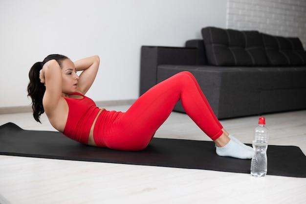 自宅で運動やヨガをしている赤いトラックスーツの若い女性