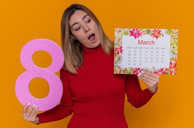 月の行進の紙のカレンダーと国際女性の日行進を祝って幸せで驚きに見える段ボールから作られた8番を保持している赤いタートルネックの若い女性