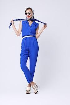 Молодая женщина в стиле ретро с солнцезащитными очками и шелковым шарфом и синим комбинезоном. женщина ретро моды стиля шестидесятых.