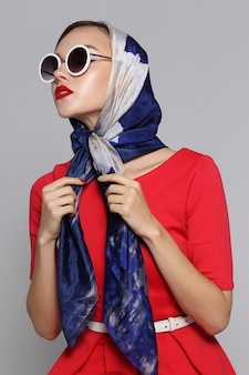 Молодая женщина в стиле ретро с очками и шелковым шарфом. женщина ретро моды стиля шестидесятых.