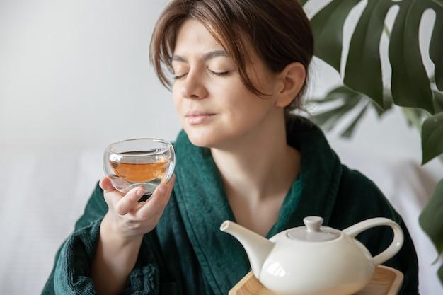 スパトリートメントとリラクゼーションのお茶の概念を楽しんでいるローブの若い女性