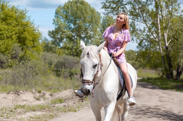 夕方の日没の光の中で彼女の白い馬とのロマンチックなドレスの若い女性。ファッションモデルの女の子との屋外写真。