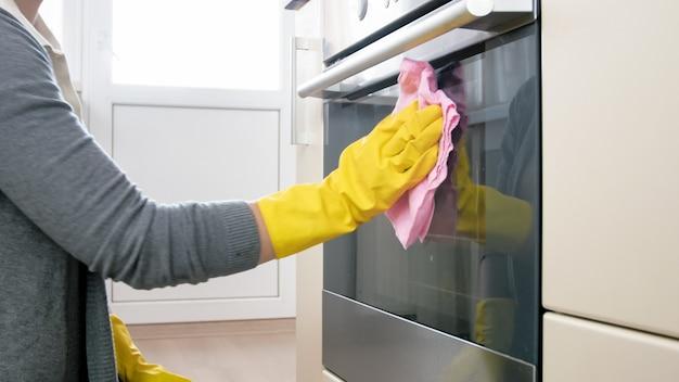 布と洗剤でキッチンを掃除するゴム手袋の若い女性。