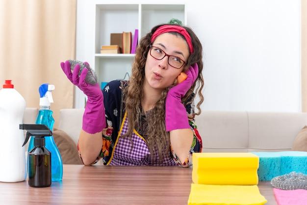 Молодая женщина в резиновых перчатках счастлива и радостно сидит за столом с чистящими средствами и инструментами в светлой гостиной