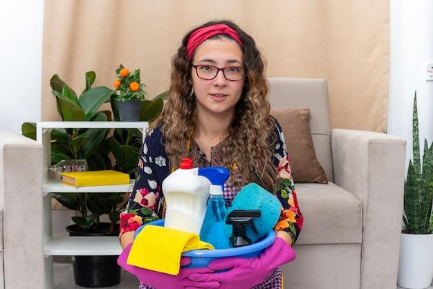 청소 용품으로 분지를 들고 고무 장갑에 젊은 여자가 행복하고 긍정적 인 가벼운 거실 바닥에 앉아 집을 청소하려고
