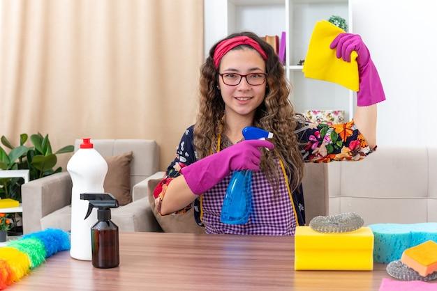 ぼろを持ち、掃除用スプレーを持ったゴム手袋をはめた若い女性が、明るいリビングルームに掃除用品と道具を置いてテーブルに座り、幸せでポジティブな笑顔を見せる