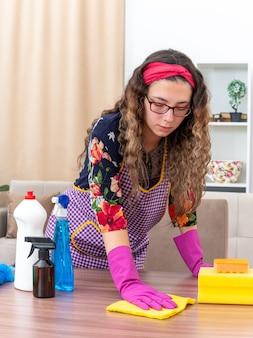 明るいリビング ルームで自信を持ってテーブルを拭くクリーニング用品でぼろを保持しているゴム手袋の若い女性