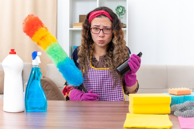 Молодая женщина в резиновых перчатках держит статический пылесос и чистящий спрей, выглядит смущенным и недовольным, сидя за столом с чистящими средствами и инструментами в светлой гостиной