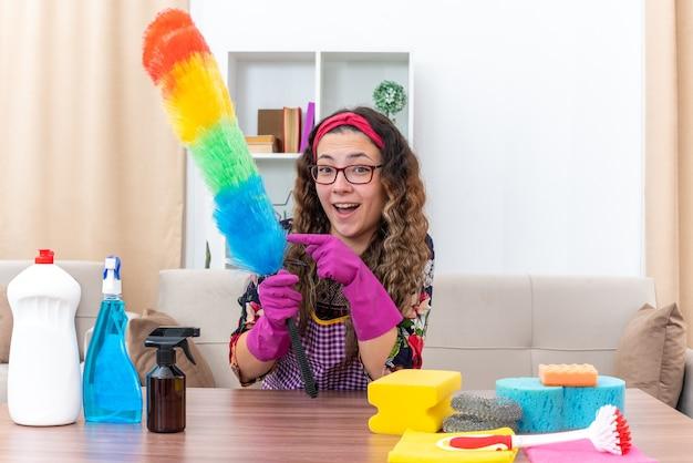 人差し指で指している静電気のダスターを保持しているゴム手袋をはめた若い女性は、明るいリビングルームに掃除用品や道具を置いてテーブルに座って、幸せで陽気な掃除の準備ができている