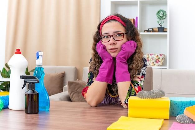 Молодая женщина в резиновых перчатках смотрит в сторону уставшая и скучающая, сидя за столом с моющими средствами и инструментами в светлой гостиной