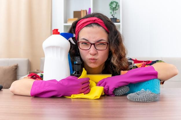 ゴム手袋をはめた若い女性が、明るいリビングルームで掃除用品や道具を持ってテーブルに座ってイライラしてイライラするカメラを見て
