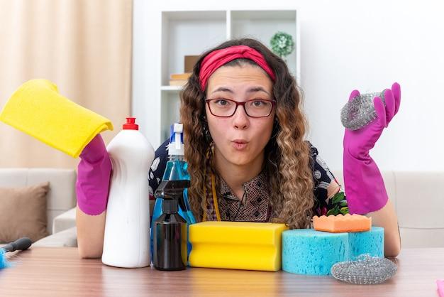 カメラを見ているゴム手袋の若い女性は、明るいリビングルームで掃除用品や道具とテーブルに座って混乱しました