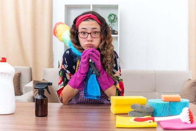 Молодая женщина в резине, держащая чистящий спрей и статический тряпщик, смотрит в растерянных перчатках, сидя за столом с чистящими средствами и инструментами