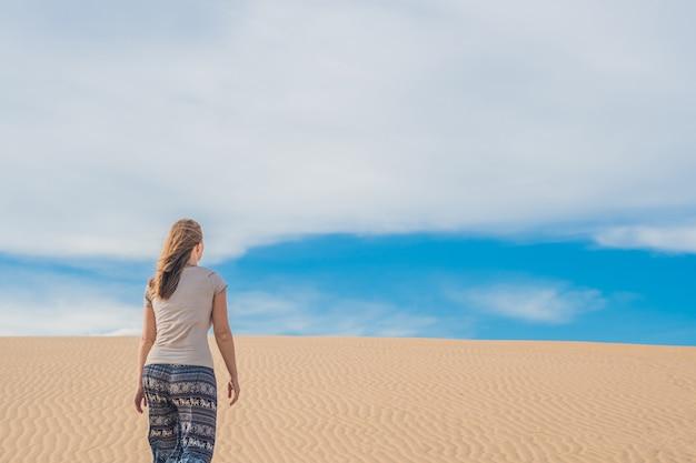 Молодая женщина в песчаной пустыне гуляет одна против заката облачного неба
