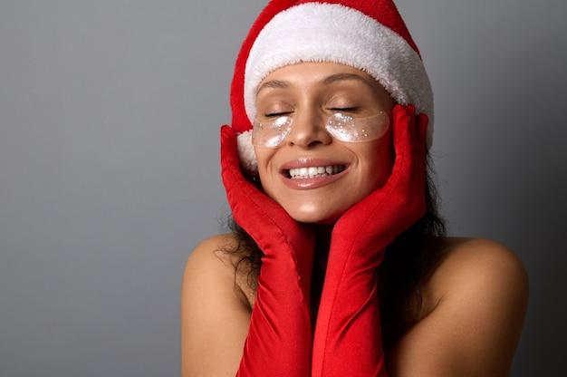 サンタカーニバルの衣装を着た若い女性は、目の下に光沢のあるスムージングスポットがあり、顔の近くで手を握り、美しい歯を見せる笑顔で笑顔を見せ、灰色の背景に目を閉じてポーズをとっています