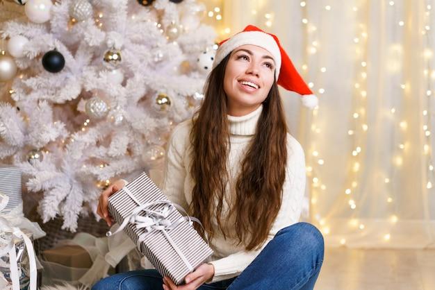 自宅でサンタクロースの帽子をかぶった若い女性が彼女の手に贈り物を持って床に座って、白人のギを笑顔...