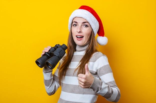 노란색 배경에 쌍안경으로 산타 클로스 모자에 젊은 여자.
