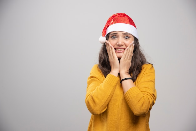Молодая женщина в красной шляпе санта-клауса позирует над белой стеной.