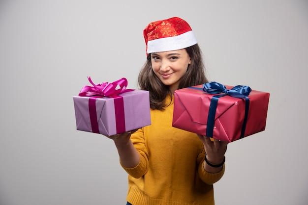 クリスマスプレゼントとサンタクロースの赤い帽子の若い女性。