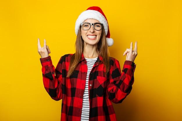 Молодая женщина в шляпе санта-клауса и красной клетчатой рубашке делает жест рок-н-ролла