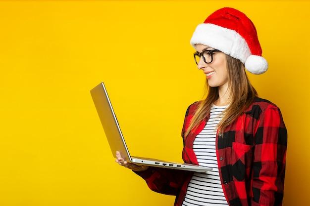 Молодая женщина в шляпе санта-клауса и красной рубашке в клетке держит ноутбук