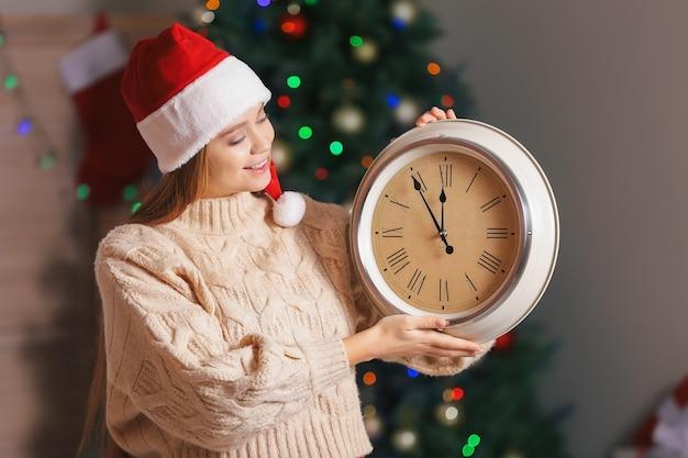 Молодая женщина в шляпе санты и с часами в комнате. концепция обратного отсчета рождества