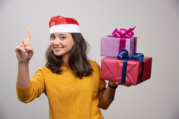 Молодая женщина в шляпе санты, несущей рождественские подарки.