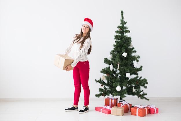 - コピー スペースを持つ白い背景にたくさんの贈り物を保持しているサンタ帽子の若い女性
