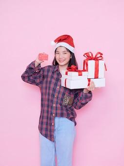 Молодая женщина в шляпе санты, держащей кредитную карту и подарочные коробки на розовой стене.