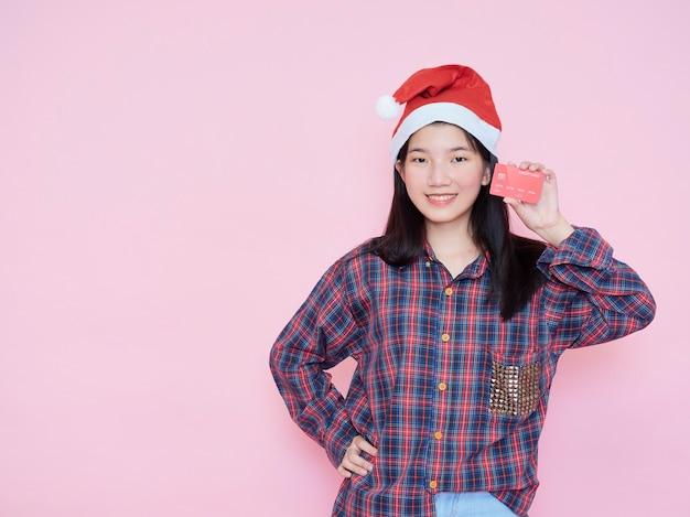 ピンクの壁にクレジットカードを保持しているサンタの帽子の若い女性。