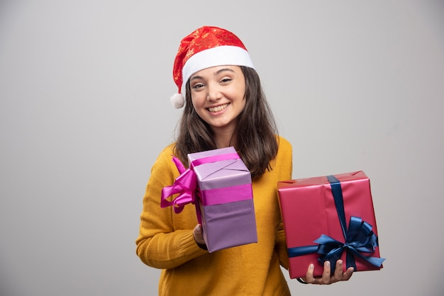 Молодая женщина в шляпе санты, держащей подарочные коробки.