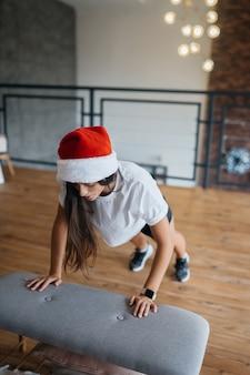 스포츠 체조 연습을 연습하는 산타 모자에 젊은 여자