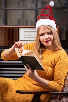本を読んでサンタの帽子をかぶった若い女性。