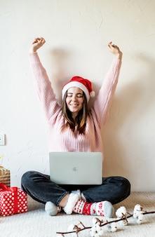 Молодая женщина в шляпе санта-клауса делает покупки онлайн в окружении подарков